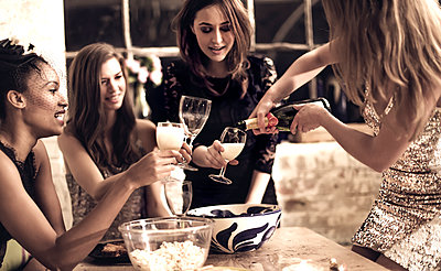 A group of women at a party, pouring and drinking champagne.  - p1100m1482295 by Mint Images