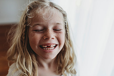 Portrait of young freckled smiling girl missing tooth with eyes closed - p1166m2130914 by Cavan Images