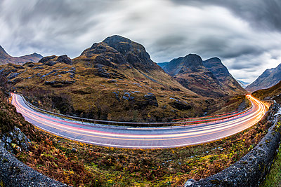 UK, Scotland, car light trails on scenic road through the mountains in the Scottish highlands near Glencoe at dusk - p300m2013255 by William Perugini