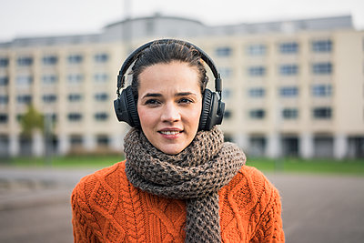 Portrait of smiling woman wearing scarf and orange knit pullover listening music with headphones - p300m2070601 von Robijn Page