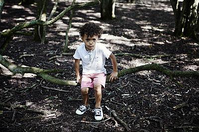 Boy sitting on branch - p312m974945f by Johanna Nyholm