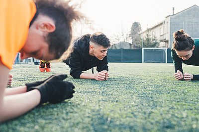 Football players in plank position on pitch - p429m1578517 by Eugenio Marongiu