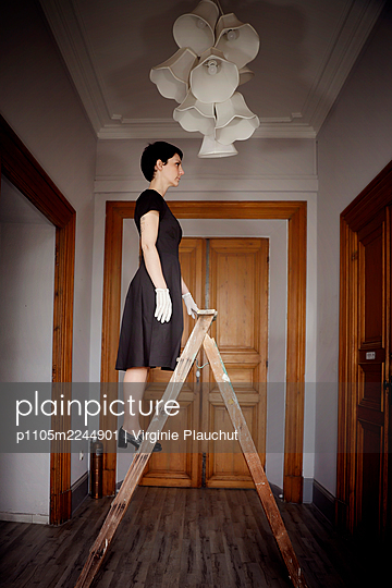 Woman in black dress on a ladder - p1105m2244901 by Virginie Plauchut