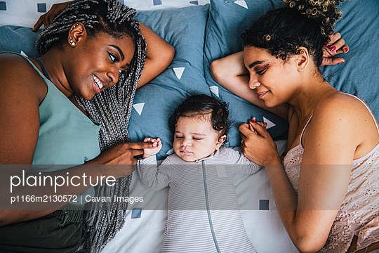 High angle view of loving lesbian mothers holding son's hands while lying on bed at home - p1166m2130572 by Cavan Images