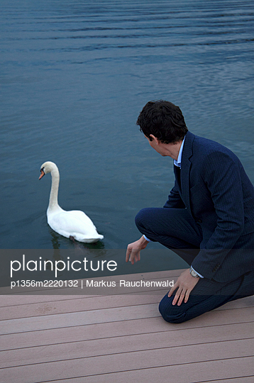 Man with swan - p1356m2220132 by Markus Rauchenwald