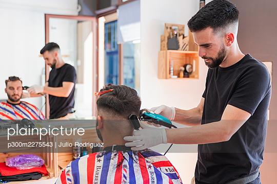 Hairdresser cutting a man's hair with a machine, Matalascañas, Spain - p300m2275543 von Julio Rodriguez
