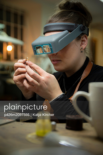 Female jeweler looking at gold through headband magnifier in workshop - p426m2097335 by Katja Kircher