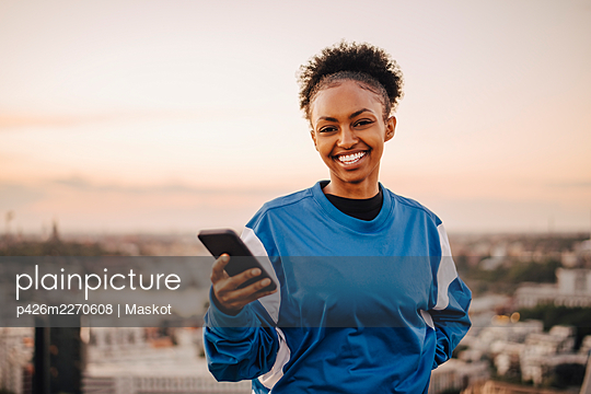 Portrait of smiling sportswoman holding smart phone during sunset - p426m2270608 by Maskot