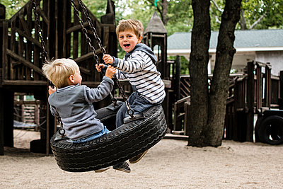 Happy brothers enjoying on tire swing in playground - p1166m1186028 by Cavan Images