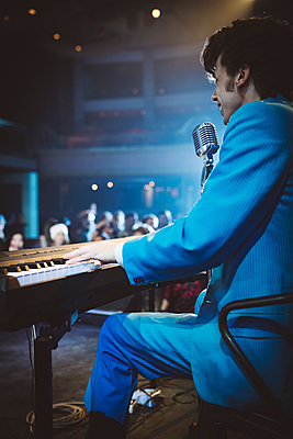 Rockabilly musician playing electric piano and singing into microphone at music concert - p1192m1567145 by Hero Images