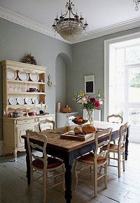 Roger Lascelles clock beside window above vegetables in Georgian townhouse kitchen - p349m789882 by Brent Darby