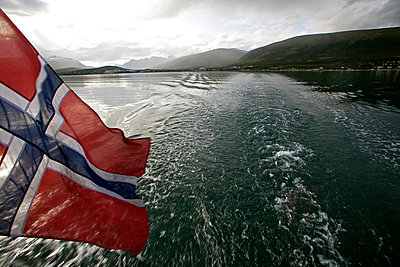 Norway, Tromso Region, sailing on a summer day through the Norwegian fjords out from the port of Tromso - a Norwegian flag flying off the stern - p6521446 by Mark Hannaford