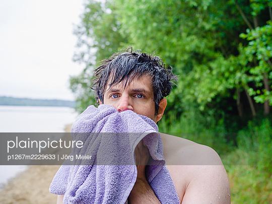 Man on the lakefront towels himself - p1267m2229633 by Jörg Meier