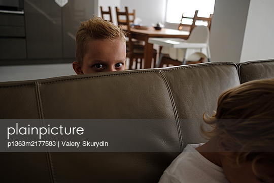 Boy is hiding behind the sofa - p1363m2177583 by Valery Skurydin