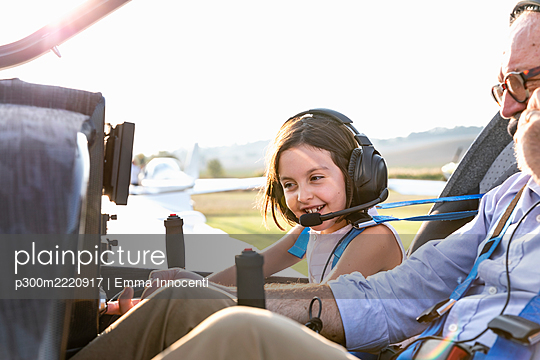Young little girl inside aircraft cockpit with grandfather at airfield on sunny day - p300m2220917 by Emma Innocenti
