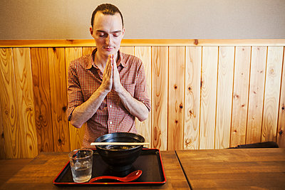 A western man in a noodle restaurant with his hands in prayer and eyes closed, saying a traditional Itadakimasu before his meal.  - p1100m1531126 by Mint Images