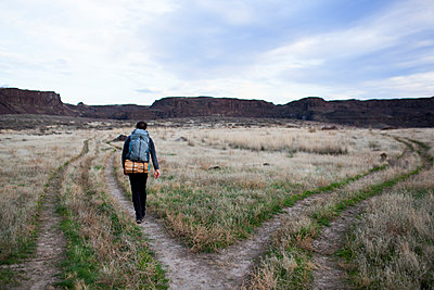 Rear view of hiker with backpack walking on field against sky - p1166m1486229 by Cavan Images