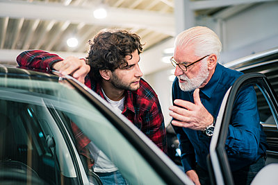 Car dealer showing car to young man in showroom - p300m2167394 by Robijn Page