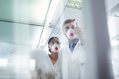 Scientists in isolation environment wearing masks, working in research laboratory. - p429m2200756 by Monty Rakusen