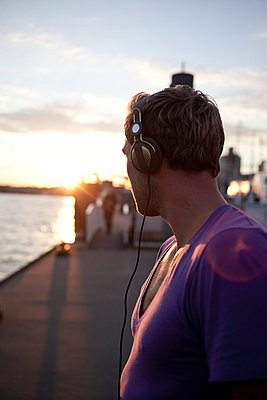 Man with headphones at a harbour - p6420186 by brophoto