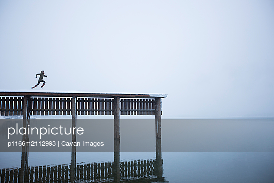 Woman running on a snowy pier on a moody winter day in Idaho. - p1166m2112993 by Cavan Images