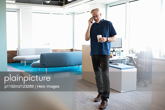 Portrait of senior business owner on cell phone in office - p1192m2123289 by Hero Images
