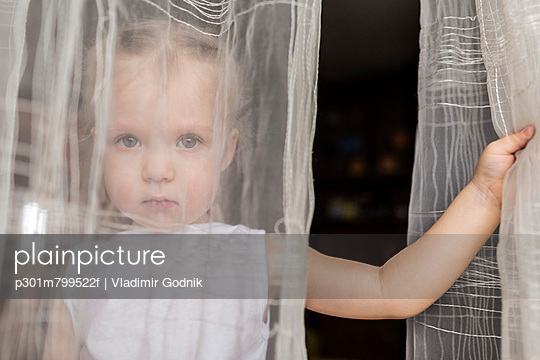 Girl staring behind translucent curtains - p301m799522f by Vladimir Godnik
