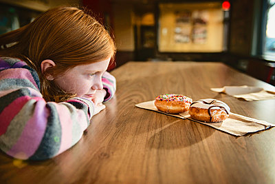 Young Red Haired Girl Looking Longingly at Delicious Doughnuts - p1166m2147604 by Cavan Images