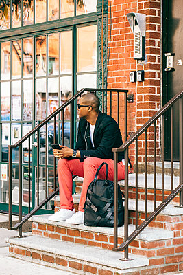 USA, NYC, Brooklyn, Man waiting on stairs, using smartphone - p300m2012668 by Visualspectrum