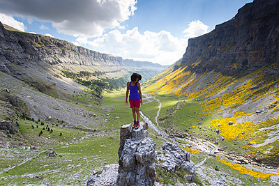 Woman standing on rock pillar in Ordesa valley in Pyrenees, Ordesa y Monte Perdido National Park, Huesca, Aragon, Spain - p343m2032595 by Aurora Photos