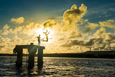 Backlit local boys jumping into the water of the lagoon of Wallis from a platform, Wallis and Futuna, Pacific - p871m1221576 by Michael Runkel