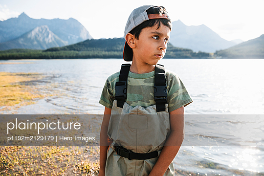 Boy fishing at sunny lake - p1192m2129179 by Hero Images