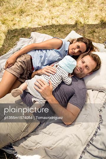 Familie mit Baby entspannt sich am Seeufer - p1355m1574054 von Tomasrodriguez
