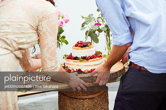 Brautpaar trägt Hochzetstorte - p432m2007496 von mia takahara