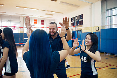 Teenage girls celebrating with male coach in court - p1166m1087825f by Andrew Lipovsky