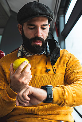 Businessman checking time while having fruit in bus during COVID-19 - p300m2242672 by Josu Acosta