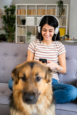 Smiling young woman listening to music through wireless headphones at home - p300m2265257 by Giorgio Fochesato