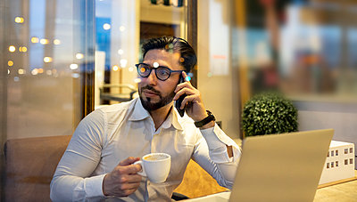 Businessman talking on smart phone while holding coffee cup in cafe - p300m2266372 by Jose Carlos Ichiro