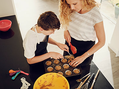 UK, London, Mother and son home baking in the kitchen filling muffin tin overhead. - p300m2282764 von Phillip Waterman