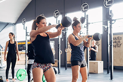 Woman weightlifting with kettle bells in gym - p429m1569245 by Eugenio Marongiu