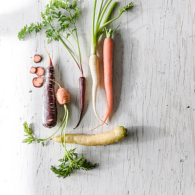 Variety of carrots on white wooden table - p555m1303824 by Manny Rodriguez