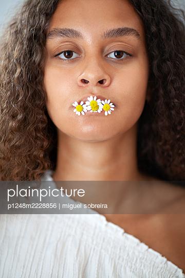 Frau mit Gänseblümchen im Mund - p1248m2228856 von miguel sobreira