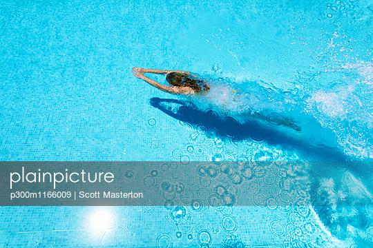 Woman diving underwater in swimming pool - p300m1166009 by Scott Masterton