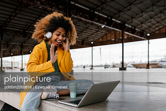 Cheerful Afro woman with in-ear headphones waving hand during video call through laptop in seating area - p300m2265816 by Ezequiel Giménez