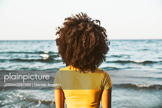 Back view of a young black woman on the beach looking the sea Riccione, Emilia Romagna, Italy People and travel concept - p300m2287250 von Davide Angelini