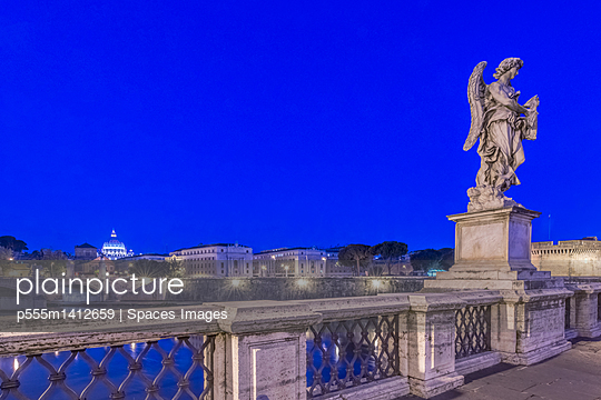 Statue over illuminated bridge at night, Rome, Italy