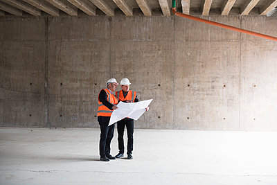 Two men with plan wearing safety vests talking in building under construction - p300m1460361 by Daniel Ingold