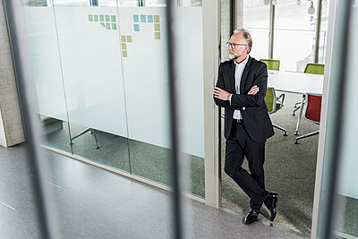 Mature businessman standing in office thinking - p300m1562367 by Uwe Umstätter