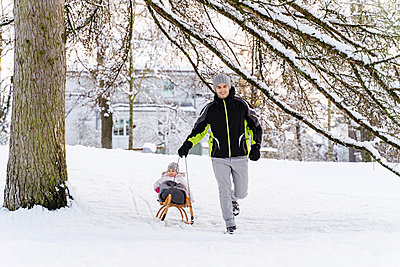 Happy father with daughter on sledge in winter landscape - p300m2083168 von Daniel Ingold
