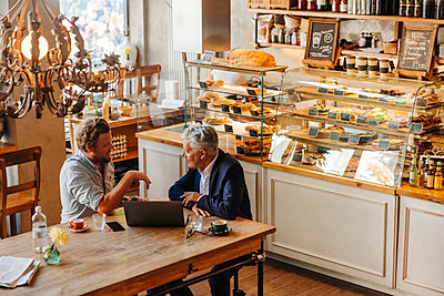 Two businessmen with laptop meeting in a cafe - p300m2140032 by Gustafsson